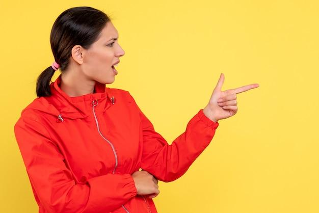Вид спереди молодая женщина в красном пальто разговаривает с кем-то на желтом фоне