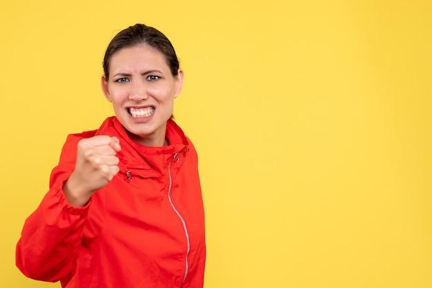 黄色の背景に怒っている顔と赤いコートの若い女性の正面図
