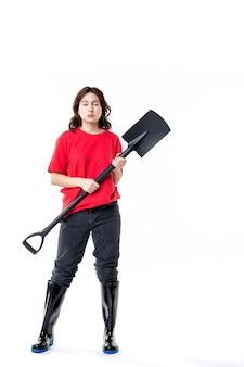 전면 보기 흰색 배경에 검은 삽을 들고 빨간 셔츠에 젊은 여성 토양 색상 작업 여자 감정 묘지 바닥