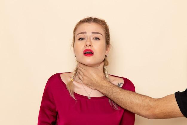 Молодая женщина в красной рубашке, вид спереди, страдает от физических угроз и насилия на кремовой космической женской ткани.