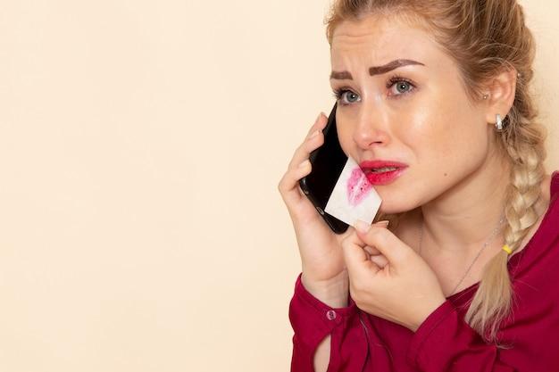 明るい空間の暴力に電話で話している赤シャツの若い女性の正面図