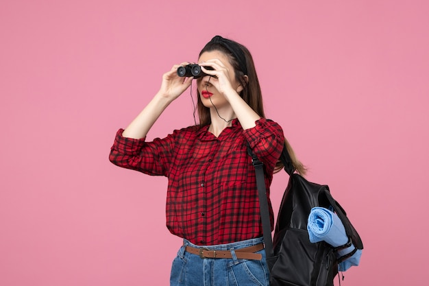 분홍색 배경 학생 색 여자에 쌍안경을 사용하는 빨간 셔츠에 전면보기 젊은 여성