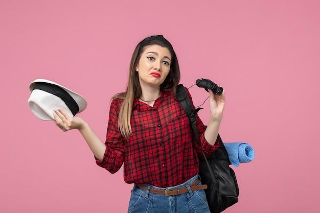 분홍색 배경 색상 여자 인간에 쌍안경을 사용하는 빨간 셔츠에 전면보기 젊은 여성