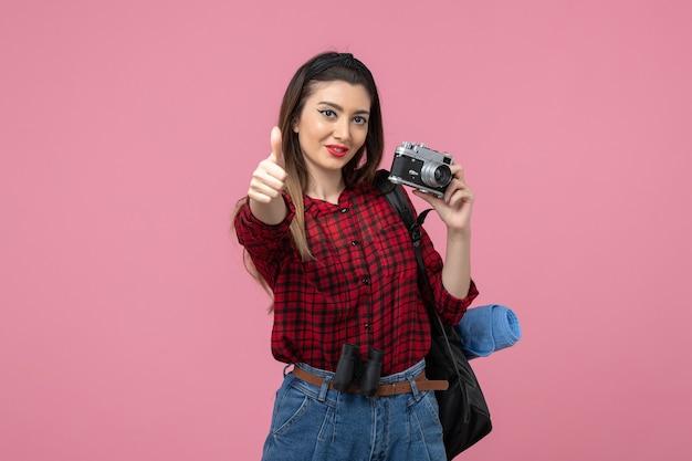 ピンクの背景モデル写真の女性にカメラと赤いシャツの正面図若い女性