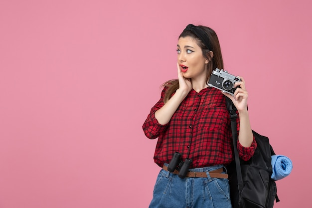 ピンクの背景の写真の女性モデルにカメラと赤いシャツを着た若い女性の正面図