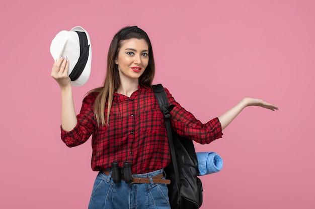 밝은 분홍색 배경 인간의 색 여자에 모자와 빨간 셔츠에 전면보기 젊은 여성