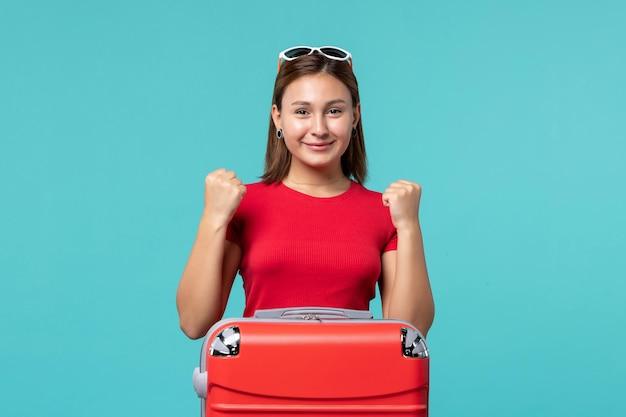 青い机の上で休暇の準備をしている赤いバッグと赤いシャツの正面図若い女性