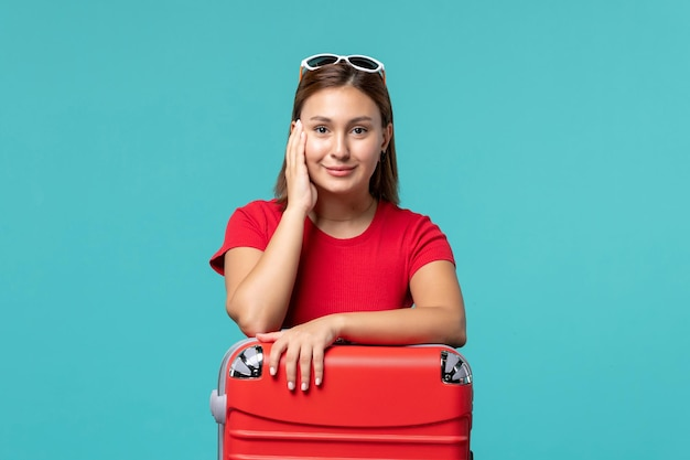 青いスペースで休暇の準備をしている赤いバッグと赤いシャツの正面図若い女性