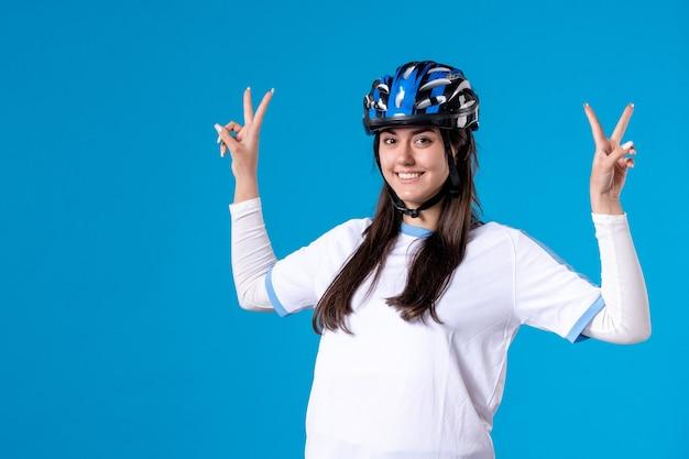 Вид спереди молодая женщина в спортивной одежде и шлеме на синей стене