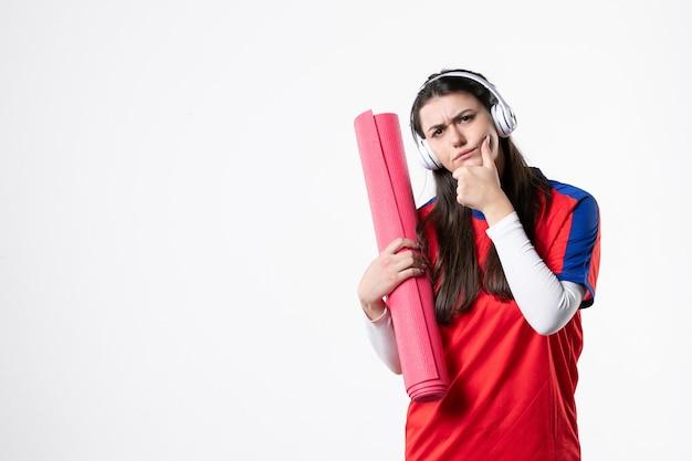 Вид спереди молодая женщина в спортивной одежде, держащая коврик для йоги