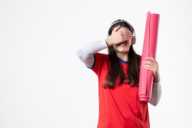 ヨガマットを保持しているスポーツ服の若い女性の正面図