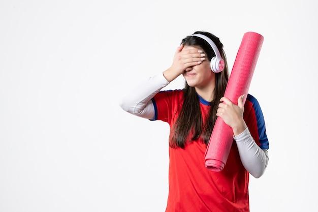 요가 매트를 들고 스포츠 옷 전면보기 젊은 여성