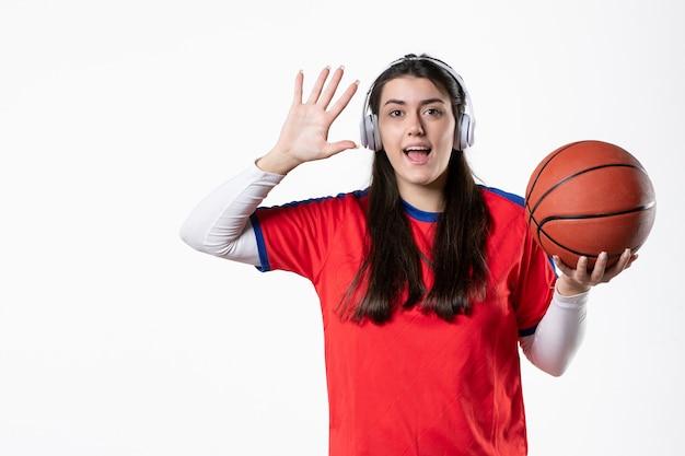 Вид спереди молодая женщина в спортивной одежде с баскетбольной белой стеной