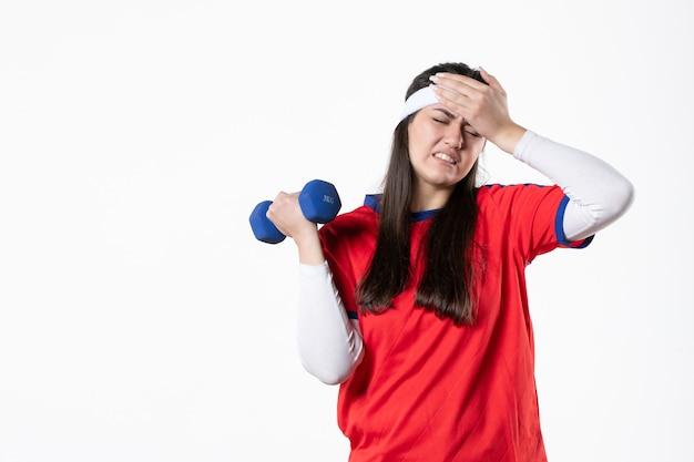 Вид спереди молодая женщина в спортивной одежде с синими гантелями на белой стене