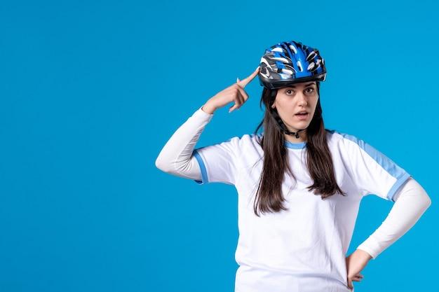青い壁にヘルメットとスポーツ服を着た若い女性の正面図