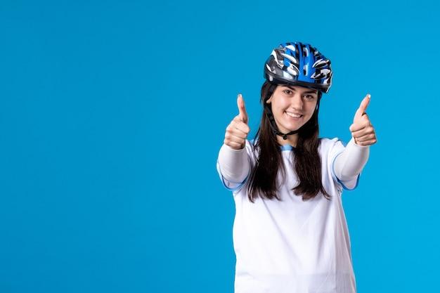 Вид спереди молодая женщина в спортивной одежде со шлемом на синей стене