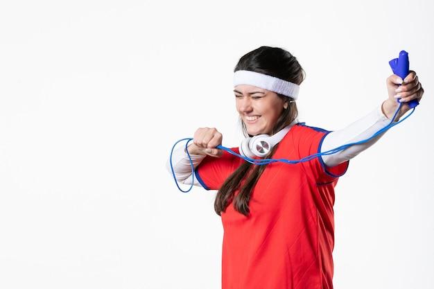 흰 벽에 밧줄을 건너 뛰는 스포츠 옷 전면보기 젊은 여성