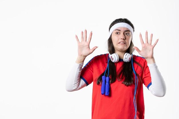 白い壁に縄跳びとスポーツ服を着た若い女性の正面図