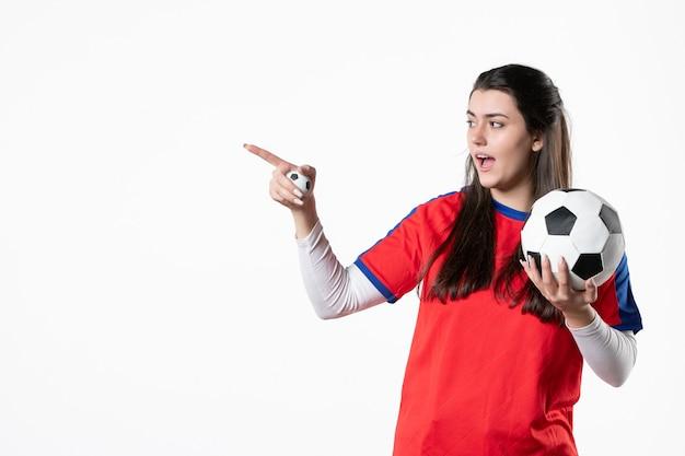 白い壁にサッカーボールとスポーツ服の若い女性の正面図