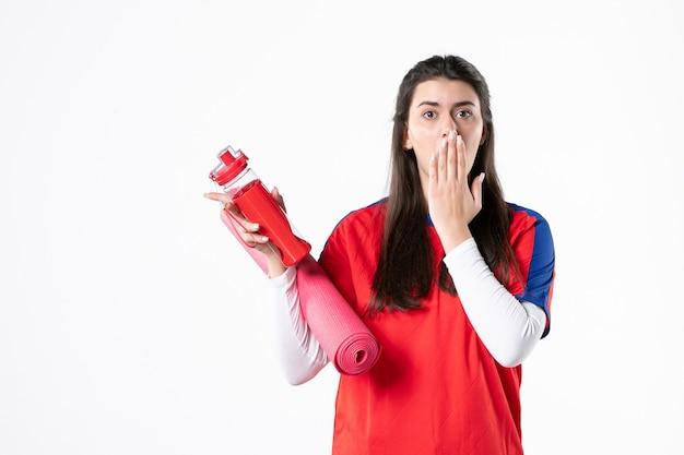 正面図白い壁にヨガマットと水のボトルとスポーツ服を着た若い女性