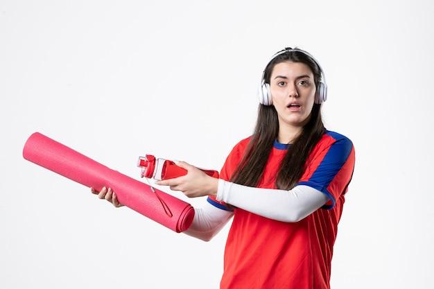 음악 흰 벽을 듣고 요가 매트와 스포츠 옷 전면보기 젊은 여성