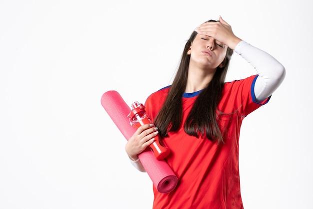 ヨガマット白い壁とスポーツ服を着た若い女性の正面図
