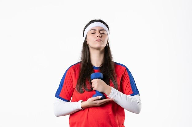 白い壁にダンベルでワークアウトスポーツ服を着た若い女性の正面図
