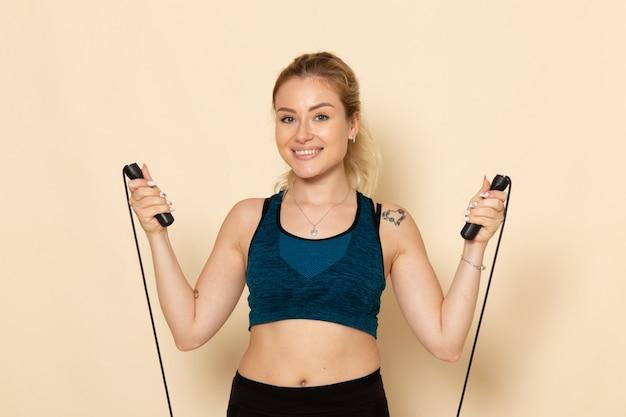밧줄을 건너 뛰는 운동을하는 스포츠 복장의 전면보기 젊은 여성