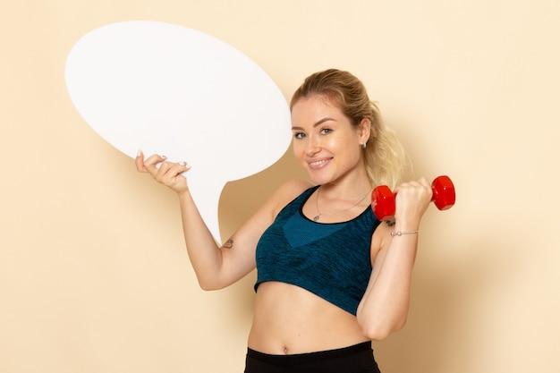 ダンベルと白い吹き出しを保持しているスポーツ衣装の若い女性の正面図