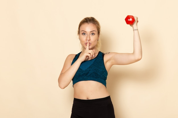 白い壁にダンベルを保持しているスポーツ衣装の正面図若い女性スポーツボディ健康美容トレーニング女性
