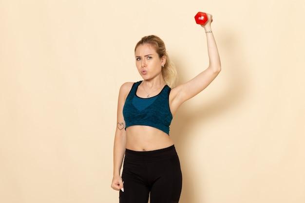 ダンベルを保持しているスポーツ衣装の若い女性の正面図