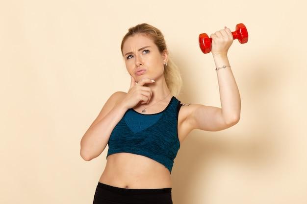 赤いダンベルを保持し、白い壁のスポーツボディ健康美容トレーニングについて考えているスポーツ衣装の若い女性の正面図