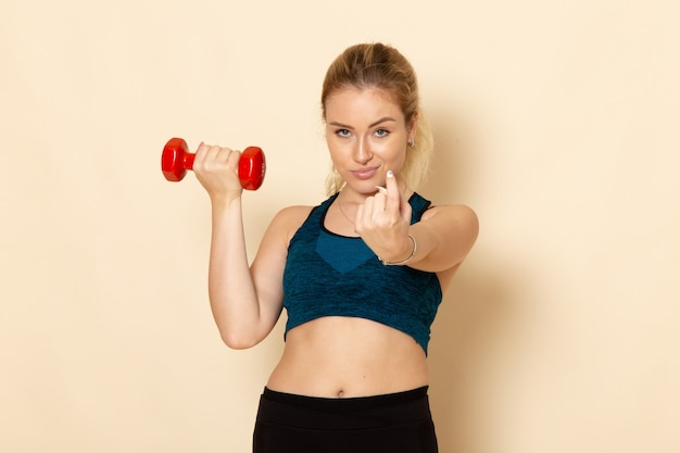 白い壁の健康スポーツボディ美容トレーニングに赤いダンベルを保持しているスポーツ衣装の若い女性の正面図