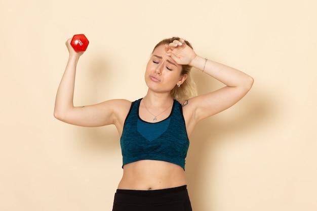 白い机の上に赤いダンベルを保持しているスポーツ衣装の正面図若い女性スポーツボディ健康美容トレーニング女性