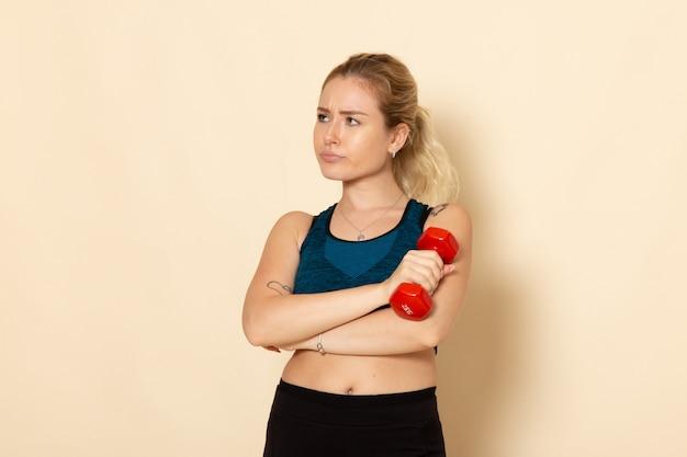 白い壁の健康スポーツボディ美容トレーニングに赤いダンベルを保持しているスポーツ衣装の若い女性の正面図 無料写真