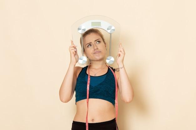 白い壁に体重計を保持しているスポーツ衣装の正面図若い女性は、体の美しさの健康スポーツ演習に適合