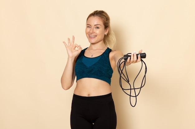 Вид спереди молодая женщина в спортивном костюме, держащая скакалки на белой стене, здоровье, красота, тренировка, телесный спорт