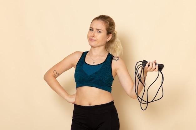 白い壁の健康トレーニングボディスポーツ美容運動に縄跳びを保持しているスポーツ衣装の正面図若い女性