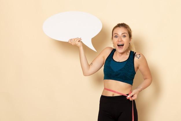 白い看板を保持し、ライトベージュの壁で彼女の体を測定するスポーツ衣装の正面図若い女性
