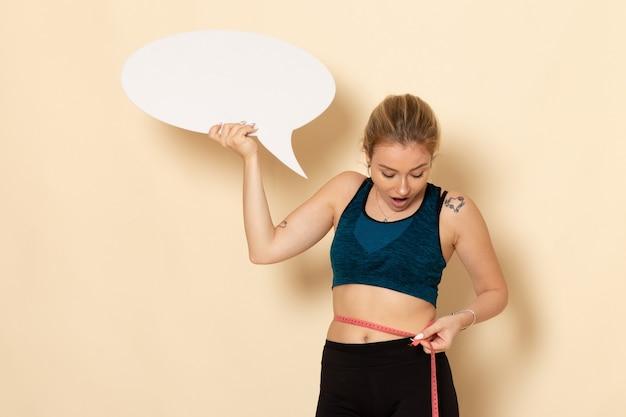 白い看板を保持し、彼女の体を測定するスポーツ衣装の若い女性の正面図