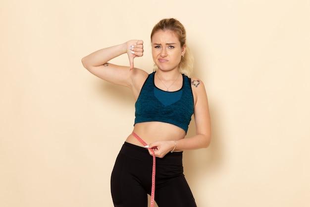 Вид спереди молодая женщина в спортивном костюме, измеряя ее тело