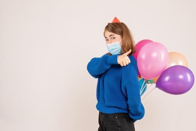 彼女の背中の後ろにカラフルな風船を隠している無菌マスクの正面図若い女性