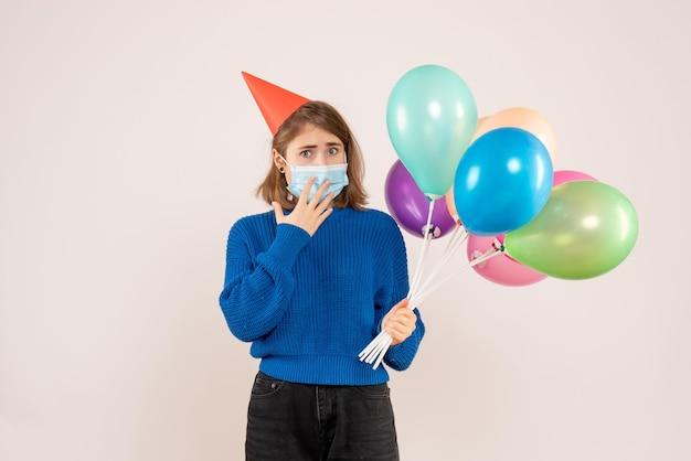 カラフルな風船を保持している無菌マスクの正面図若い女性