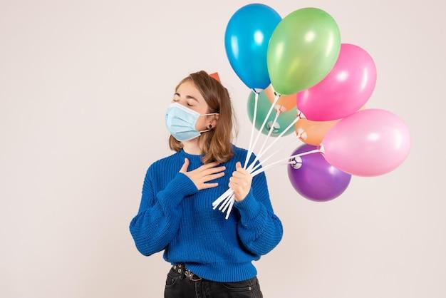 다채로운 풍선을 들고 살 균 마스크 전면보기 젊은 여성