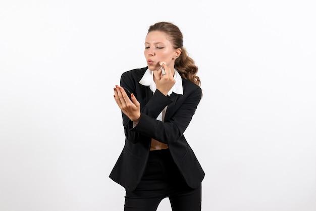 심각한 흰색 배경 여자 직업 의상 사업에 그녀의 메이크업을 하 고 엄격한 클래식 정장에 전면보기 젊은 여성