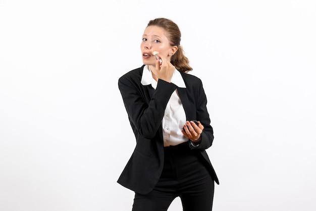Вид спереди молодая женщина в строгом классическом костюме делает макияж на светлом белом фоне женский рабочий костюм бизнес женская работа