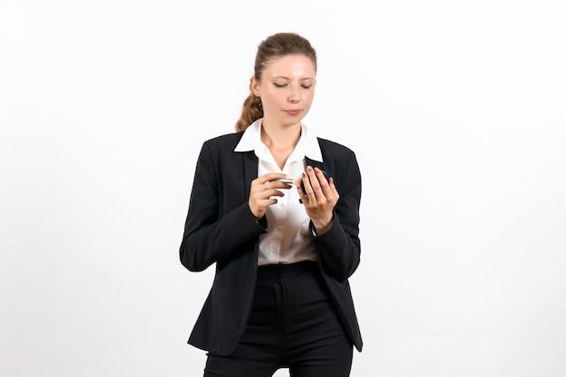 Вид спереди молодая женщина в строгом классическом костюме делает макияж на белом фоне женский рабочий костюм бизнес женская работа