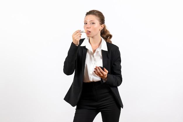 Вид спереди молодая женщина в строгом классическом костюме делает макияж на белом столе, женский рабочий костюм, деловая женская работа