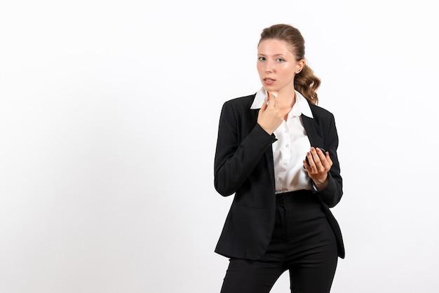 Вид спереди молодая женщина в строгом классическом костюме делает макияж на белом фоне женский рабочий костюм деловой женский рабочий