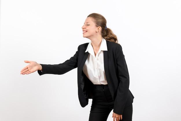 Вид спереди молодая женщина в строгом классическом костюме приветствует кого-то на белом столе деловая женщина работает женский рабочий костюм